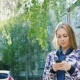 Attractive Woman Walking In The City, Enjoys a Smartphone. The Sun's Rays Fall Nice Highlights - VideoHive Item for Sale
