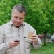 Middle-aged Man Drinking Coffee On The Go, Walking On City Park - VideoHive Item for Sale