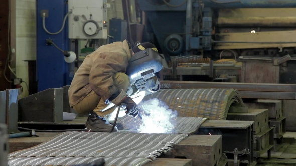 Worker Welds a Metal Sheets On a Factory