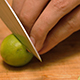 Chef Slices Key Limes on a Bamboo Cutting Board - VideoHive Item for Sale
