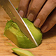 Man Scoops and Slices an Avocado on a Bamboo Cutting Board - VideoHive Item for Sale