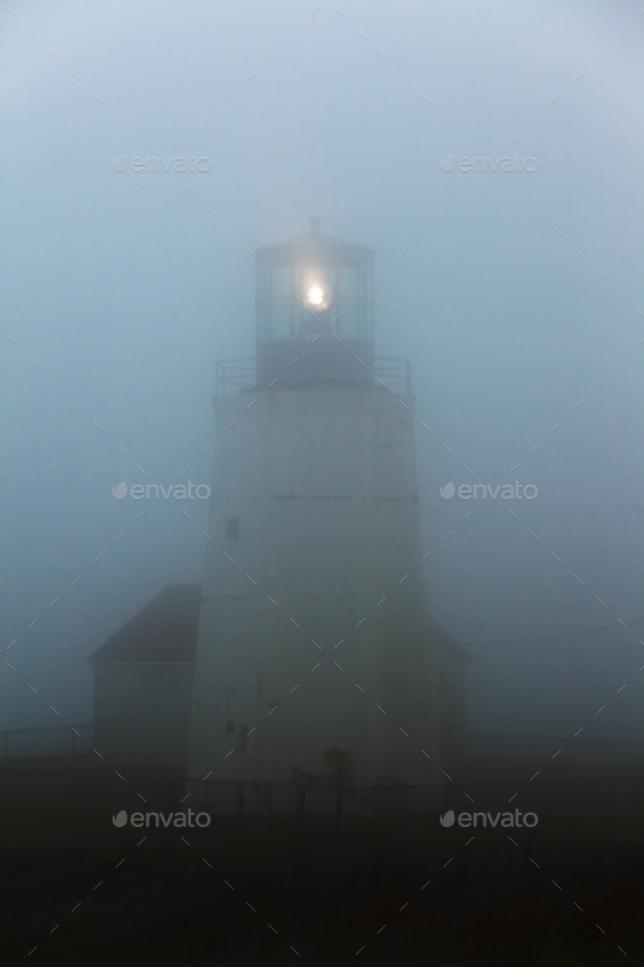 Ghostly lighthouse beacon in thick fog NL Canada - Stock Photo - Images