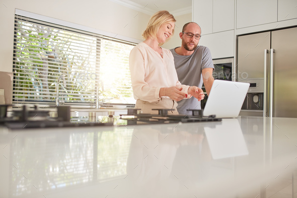 Happy couple using laptop in the kitchen at home - Stock Photo - Images