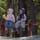 Two Young Children Eating Bananas Sitting On The Bench - VideoHive Item for Sale