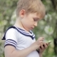 Young Little Boy Plays Games On Smartphone. Spring Tree - VideoHive Item for Sale