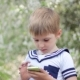 Young Little Boy Plays Games On Smartphone. Spring - VideoHive Item for Sale