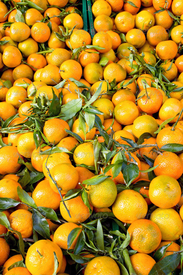 Fresh clementines with green leaves on a market - Stock Photo - Images