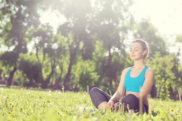Woman meditating in park - Stock Photo - Images