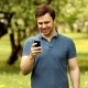 Attractive Man Using Mobile Phone In Park At The Green Background - VideoHive Item for Sale