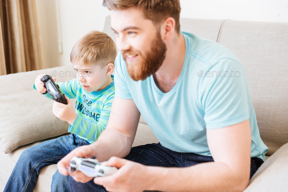 Little boy playing video games with dad sitting on sofa - Stock Photo - Images