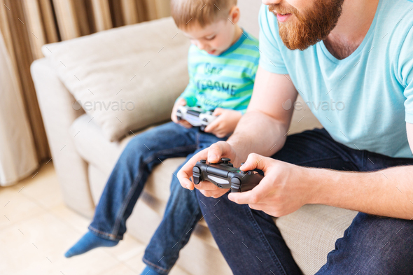 Man sitting and playing computer games with his little son - Stock Photo - Images