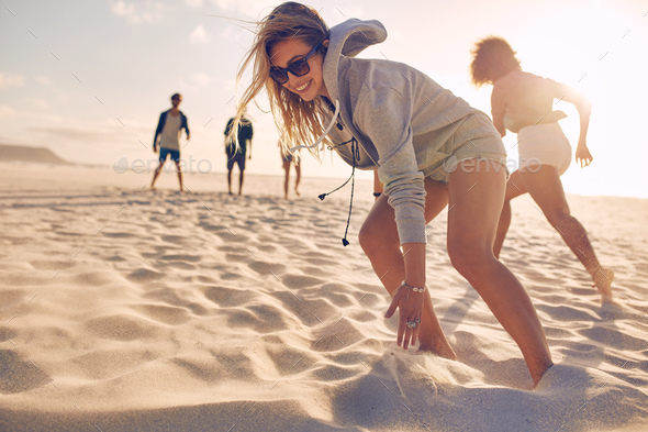 Young woman running race with friends at the beach - Stock Photo - Images