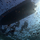 Divers Getting Into Dingy Shot From Below With Sun Breaking the Surface - VideoHive Item for Sale