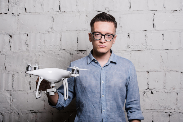 Young stylish Man in glasses holding the quadcopter drone DJI Phantom 4 on a grey brick wall - Stock Photo - Images