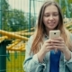 Girl With The Phone Against The Backdrop Of a Theme Park - VideoHive Item for Sale