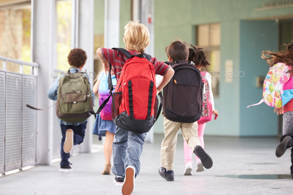 Group of elementary school kids running at school, back view - Stock Photo - Images