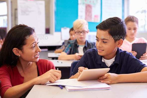 Teacher helping elementary school boy using tablet computer - Stock Photo - Images