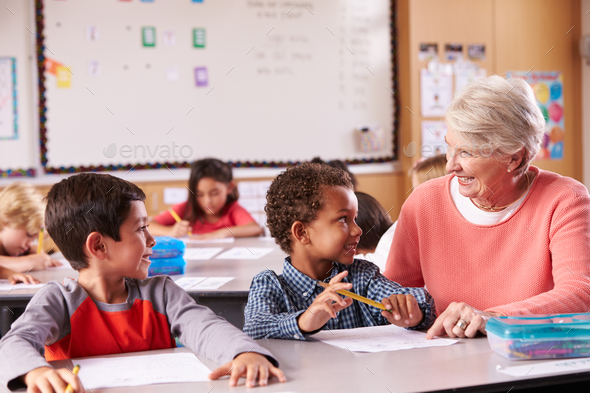 Senior teacher sitting with elementary school kids in class - Stock Photo - Images