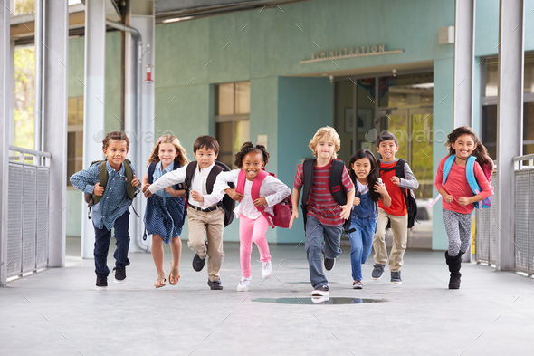 Group of elementary school kids running in a school corridor - Stock Photo - Images