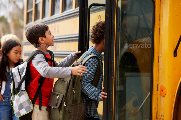 Elementary school kids climbing on to a school bus - Stock Photo - Images