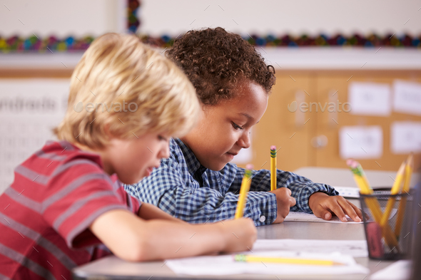 Two boys working at their desks in elementary school class - Stock Photo - Images