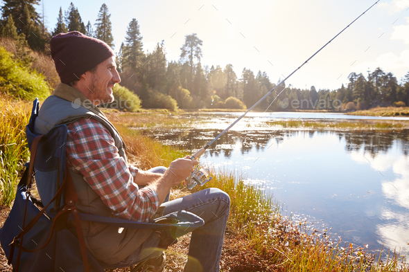 Man relaxing and fishing by lakeside, California, USA - Stock Photo - Images