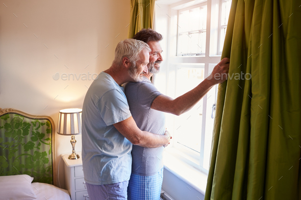 Male couple embrace looking out of their hotel room window - Stock Photo - Images