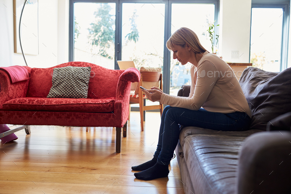 Woman Sitting On Sofa Sending Text Message On Phone - Stock Photo - Images