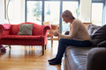 Woman Sitting On Sofa Sending Text Message On Phone - PhotoDune Item for Sale