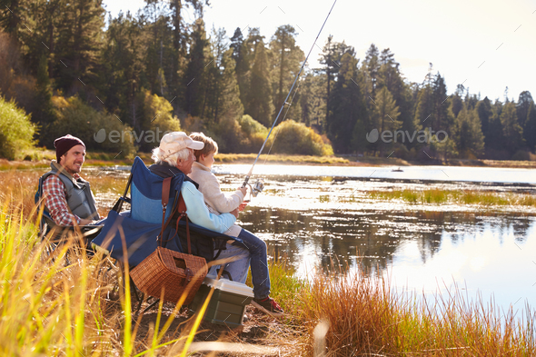 Grandad teaches his grandson to fish at a lake, dad watching - Stock Photo - Images
