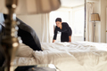 Chambermaid changing bed linen on the bed in a hotel room - PhotoDune Item for Sale