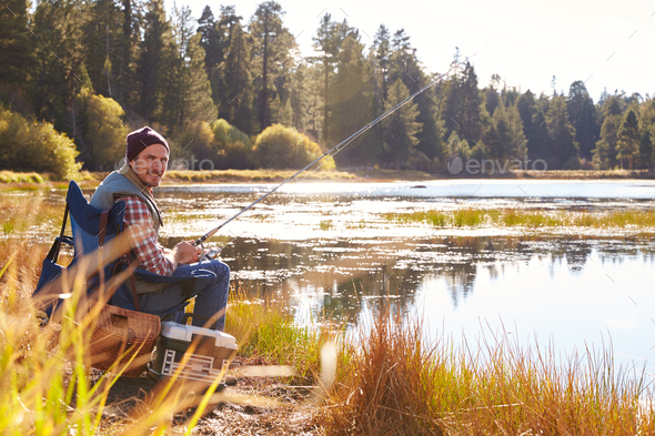 Man fishing by lakeside, looking to camera - Stock Photo - Images