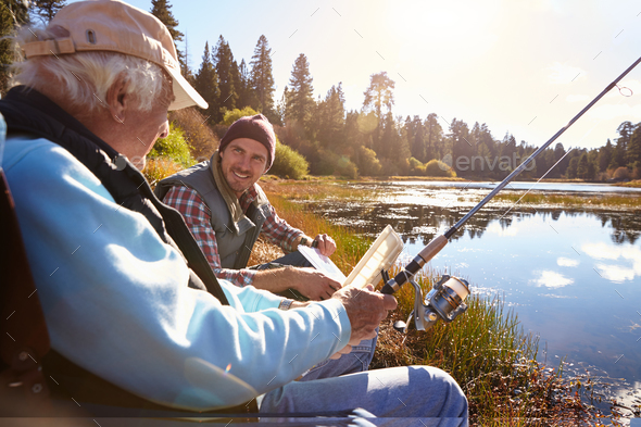 Father and adult son fishing lakeside, close-up - Stock Photo - Images