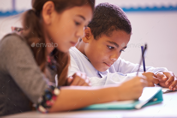 Two elementary school pupils working at desk during a lesson - Stock Photo - Images