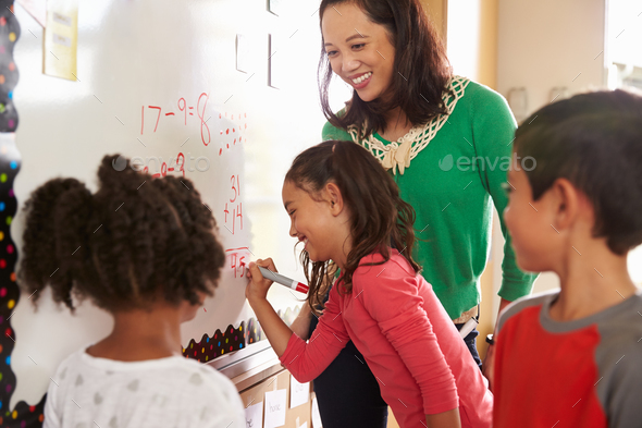 Pupil writing on the board at elementary school maths class - Stock Photo - Images