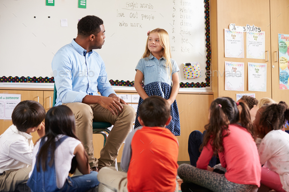 Schoolgirl at front of elementary class with teacher - Stock Photo - Images