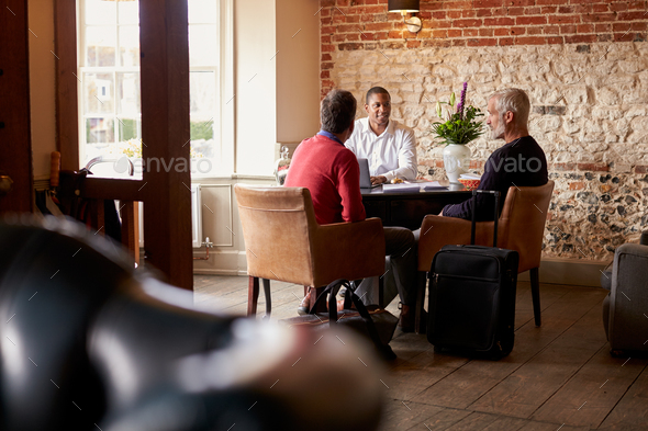 A middle aged gay male couple check in at a boutique hotel - Stock Photo - Images