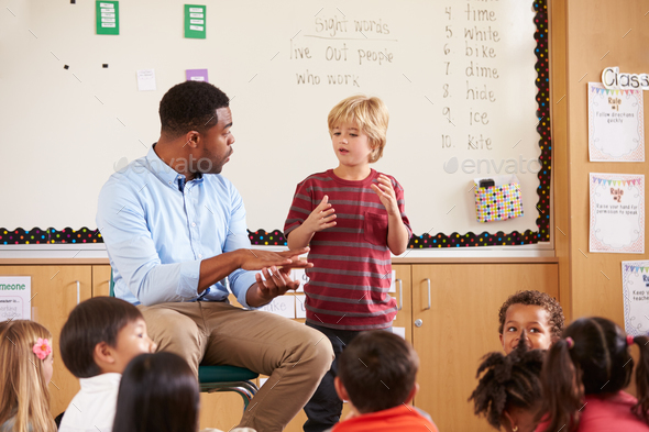 Schoolboy at the front of elementary class with teacher - Stock Photo - Images
