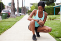 Young woman checking smart watch in the street before a run - PhotoDune Item for Sale