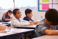 Elementary school kids working at their desks in a classroom - PhotoDune Item for Sale
