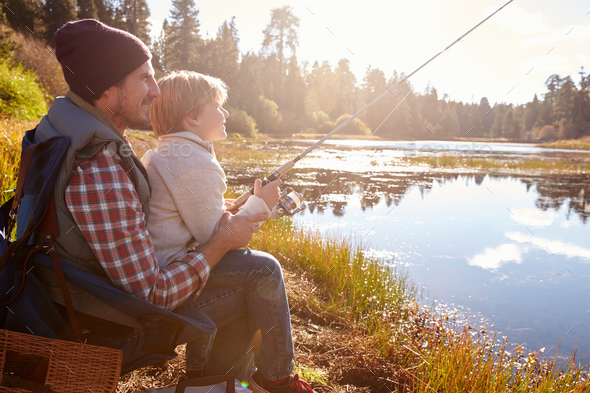 Father teaching son to fish sitting at lakeside - Stock Photo - Images