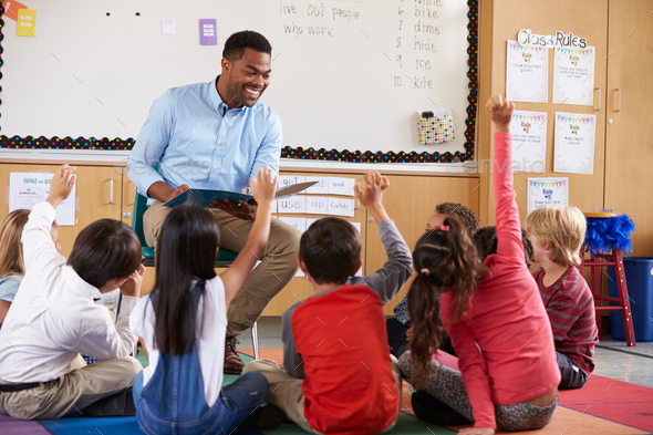 Elementary school kids sitting around teacher in a classroom - Stock Photo - Images