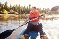 Man Wearing Life Preserver Rowing Kayak On Lake - PhotoDune Item for Sale