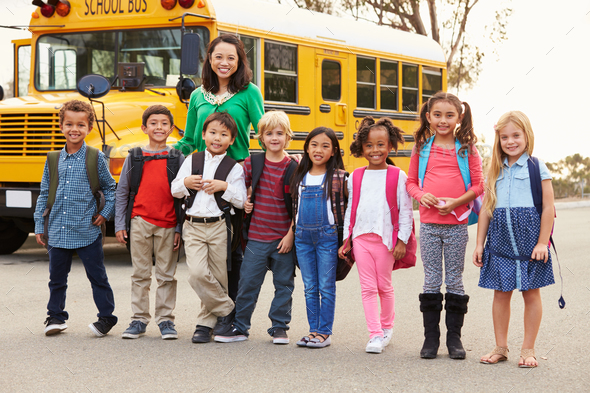 Teacher and a group of elementary school kids at a bus stop - Stock Photo - Images