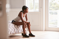 Young black woman in sports clothes sitting on bed at home - PhotoDune Item for Sale
