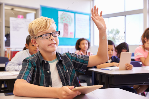 Boy with glasses raising hand in elementary school class - Stock Photo - Images