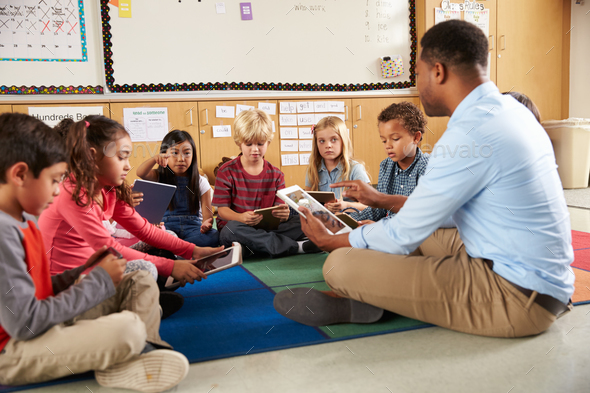 Elementary school class sitting cross legged using tablets - Stock Photo - Images