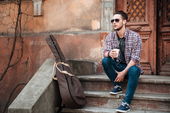 Man with cup of coffee sitting on the building stairs - Stock Photo - Images