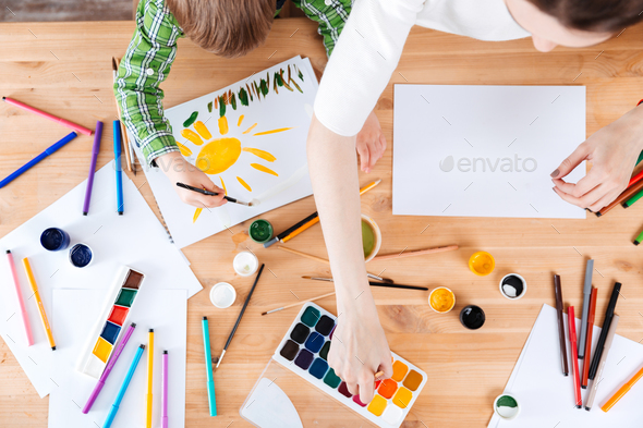 Little son and mother painting with watercolor paints on table - Stock Photo - Images