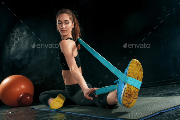 The brunette athletic woman exercising with rubber tape - Stock Photo - Images
